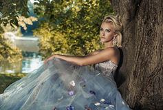 Blond young lady leaning on the tree Stock Photos