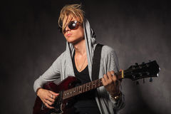 Blond young man with messy hair playing guitar in studio Royalty Free Stock Image