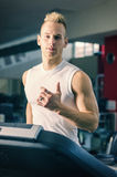 Blond young man running on treadmill Royalty Free Stock Image