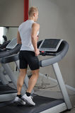 Blond young man running on treadmill Royalty Free Stock Images