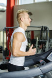 Blond young man running on treadmill Royalty Free Stock Photography