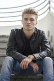 Blond young man sitting on stairs outside Stock Photography