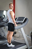 Blond young man standing on treadmill Royalty Free Stock Images