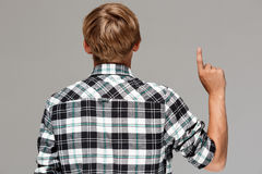 Blond young man wearing casual plaid shirt standing back to camera, pointing up with finger over grey background. Copy Stock Image