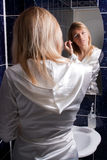 Blond young woman in bathroom applying makeup Royalty Free Stock Photos