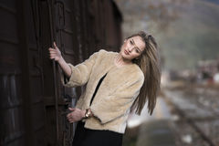 Blond young woman climbed on a wagon train. Blond young woman wear sheep jacket and black long skirt climbed on a wagon train facing the camera with smile Stock Photo