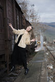 Blond young woman climbed on a wagon train. Blond young woman wear sheep jacket and black long skirt climbed on a wagon train. Full length body length vertical Stock Photos