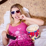 Blond young woman in color pajamas lying in bed with TV remote control in hand watching movie in 3D glasses and eating popcorn Royalty Free Stock Photo