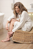 Woman depilating her leg. Blond young woman depilating her leg royalty free stock photo