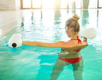 Blond young woman doing aqua aerobics Stock Image