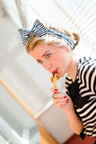 Blond young woman eating chocolate bar. Pinup pretty girl eating chocolate bar with red lips at white jalousie background image closeup Stock Photography