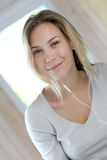 Blond young woman listening to music Royalty Free Stock Photography