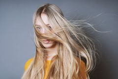 Blond woman with long windswept tousled hair. Blond young woman with long windswept tousled hair blowing into her face royalty free stock photo