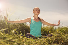 Blond young woman meditating on the nature with eyes closed Royalty Free Stock Photography