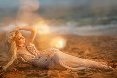 Blond young woman model with bright makeup outdoors in vogue style in evening dress behind blue sky Royalty Free Stock Photo