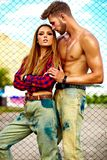Blond young woman model and handsome muscled man outdoors. Portrait of beautiful couple. Sexy stylish blond young women model with bright makeup with perfect Royalty Free Stock Image
