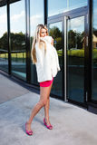 Blond young woman in pink dress and white coat posing Royalty Free Stock Images