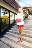 Blond young woman in pink dress and white coat posing Royalty Free Stock Photos