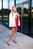 Blond young woman in pink dress and white coat posing Royalty Free Stock Image