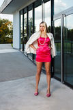 Blond young woman in pink dress and white coat posing Royalty Free Stock Photography