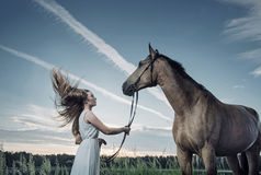Blond young woman playing with a majestic stallion stock image
