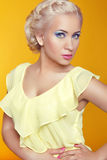 Blond young woman posing over yellow background Royalty Free Stock Images