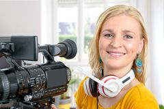 Blond young woman with professional video camera,. A blond young woman with professional video camera Royalty Free Stock Images