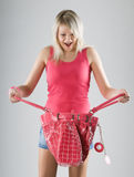 Blond young woman in red with red bag Royalty Free Stock Image