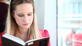 Blond young woman riding tram, reading book without glasses stock footage