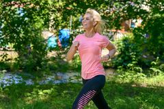 Young woman running in countryside. Blond young woman running on road in green countryside, summer scene Stock Photography
