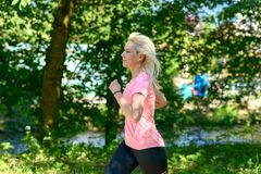 Young woman running in countryside. Blond young woman running on road in green countryside, summer scene, close up view Stock Photos