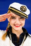Blond young woman saluting in a sea peak-cap royalty free stock photo