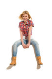 Blond young woman sitting on a banner Stock Photography
