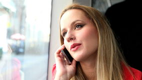 Blond young woman sitting in tram, talking on phone stock footage