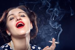 Woman smoking joint. Young woman smoking joint on black background Royalty Free Stock Photos