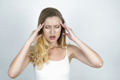 Blond young woman suffering headache holding her hands near forehead close up isolated white background royalty free stock photo