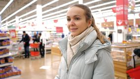 Blond young woman wanders around large modern supermarket. Pretty young blond woman with ponytail in warm jacket wanders around popular large modern supermarket stock footage
