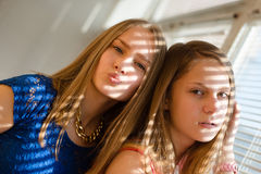 2 blond young women beautiful sisters or girl friends in blue dress having fun posing looking at camera against sun lighted rays. Two beautiful sisters or girl Stock Images