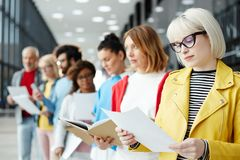 Reading resume. Blond young women in eyeglasses reading her resume while standing in queue and waiting for her turn for interview stock images