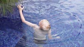 Blonda bad f?r stilig pojke i den utomhus- p?len stock video