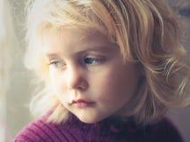 Blonda blått synade lilla flickan som ut ser fönstret Fotografering för Bildbyråer