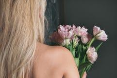 Blonda blommor för ett kvinnainnehav, sikt från henne tillbaka royaltyfria bilder