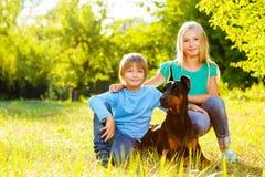 Blonda flicka- och pojkekramar älskad hund eller doberman Royaltyfri Foto