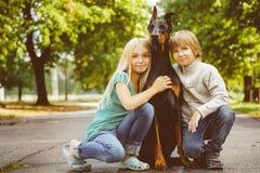 Blonda flicka- och pojkekramar älskad hund eller doberman Royaltyfri Fotografi