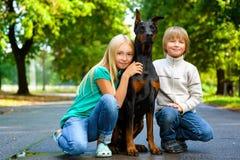 Blonda flicka- och pojkekramar älskad hund eller doberman Arkivfoto