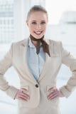 Blonda gladlynta affärskvinnaanseendehänder på höfter Arkivfoto