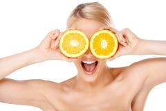 Blonda kvinnadanandeexponeringsglas med orange halfs Arkivbilder