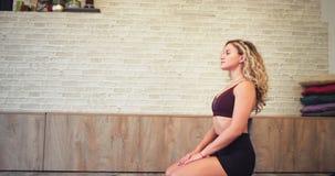 Blonda kvinnan för lockigt hår har en meditationtid i yoga som kopplar av och den koncentreras henne som öva meditationen av henn arkivfilmer