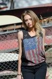 Blonda kvinnor lutar mot ett staket arkivfoton