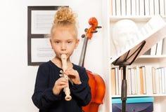 Blonda lockiga flickalekar blåser flöjt den stående near violoncellen Arkivbild